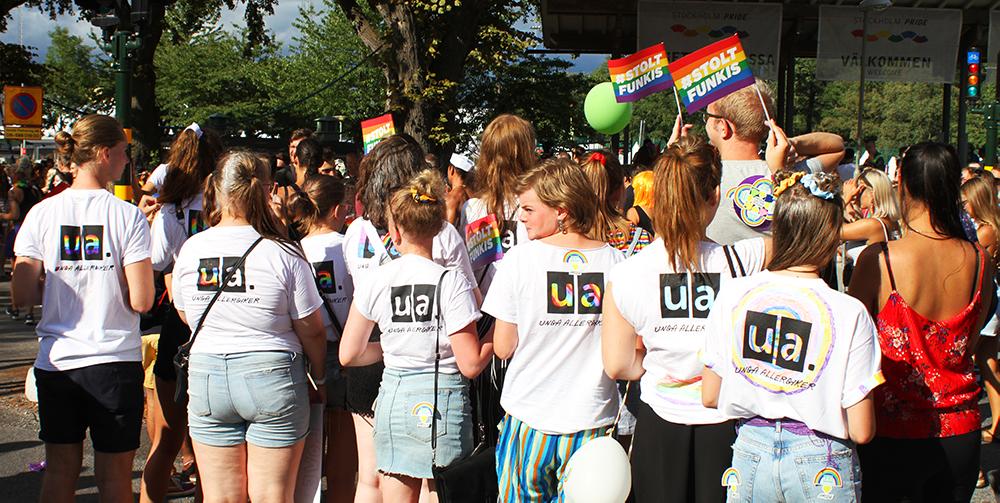 Pride 2018. Sex medlemmar står med ryggen vänd mot kameran, de har på sig vita t-shirts med Unga Allergikers logotyp. Några viftar Prideflaggor med texten #StoltFunkis.