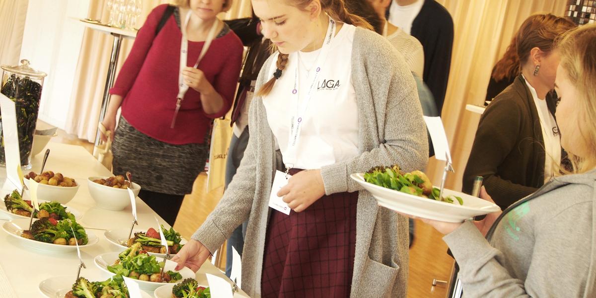 Ett bord står uppdukat med uppmärkta tallrikar med mat. En konferensdeltagare ska precis plocka upp sin tallrik. Fotot är taget på Unga Allergikers konferens för projektet Tillgängligskola.nu
