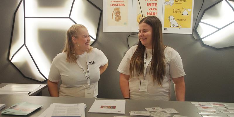 Två medlemmar står framför en informationsdisk och tittar på varandra och skrattar. Framför dem ligger informationsmaterial.