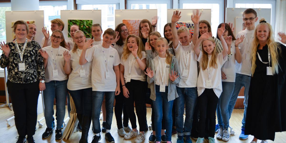 Ett tjugotal personer vinkar mot kameran och ser glada ut. Fotot är taget på Unga Allergikers och Svenska Celiakiungdomsförbundets konferens för projektet Tillgängligskola.nu.