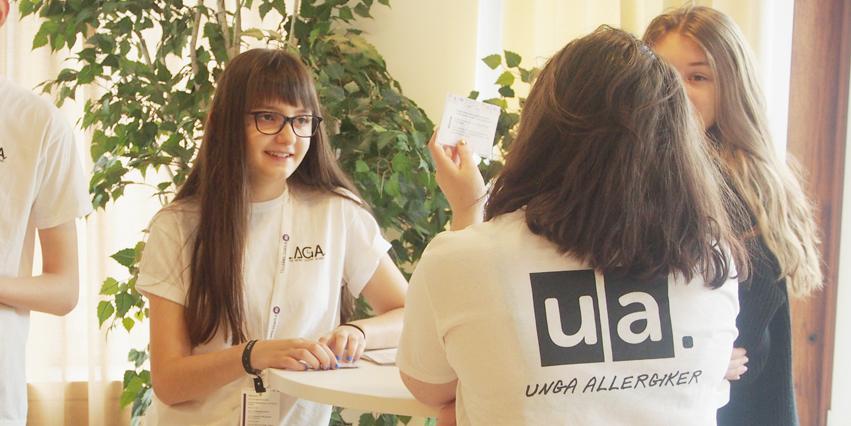 Tre medlemmar står runt ett bord och pratar. En av medlemmarna har på sig en t-shirt med Unga Allergikers logotyp på ryggen.