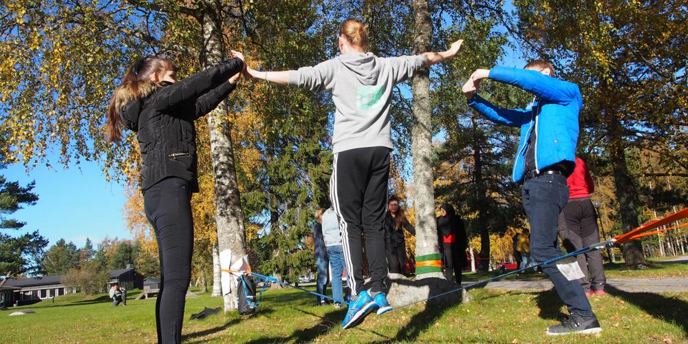 En medlem balanserar på en lina som är uppspänd mellan två träd. På vardera sida står medlemmar som hjälper till att stötta upp.