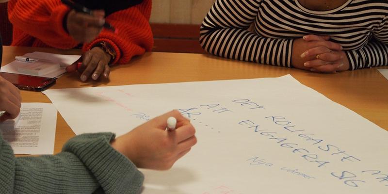 """Tre medlemmar sitter runt ett papper som det står """"Det roligaste med att engagera sig är..."""" och skriver ner olika tankar."""
