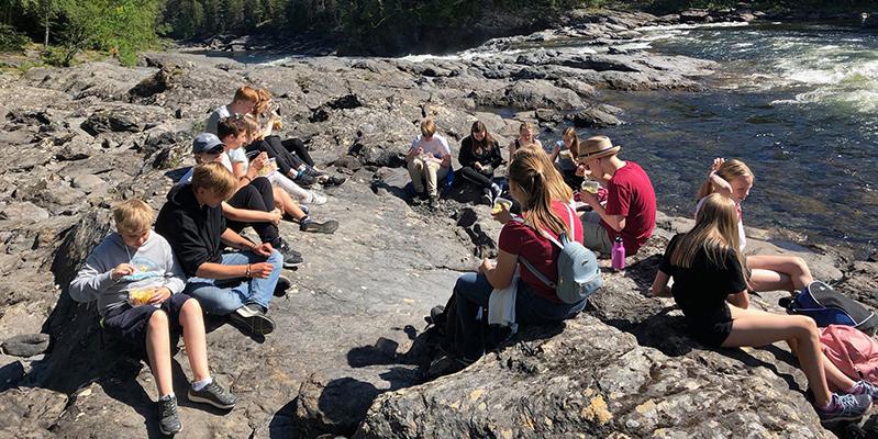 Fotot är taget på Unga Allergikers sommarläger 2018 i Åre. Ett tjugotal personer sitter på en klippa vid en fors och äter matsäck.
