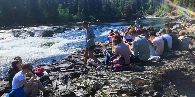 Fotot är taget på Unga Allergikers sommarläger 2018 i Åre. Ett tjugotal personer sitter vid en fors och äter matsäck.