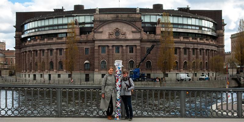 Unga Allergikers förbundsordförande Freja Anckers och Emma Grönlund, tidigare generalsekreterare, står framför riksdagen, på var sin sida om ett stort genomskinligt rör fyllt med insamlade gamla astmainhalatorer.
